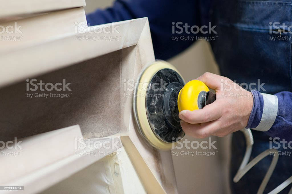 Carpenter Worker Sanding Wooden Table with Power Sander stock photo