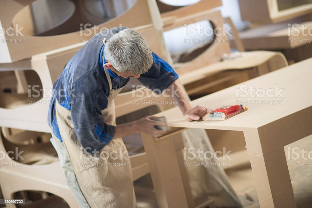 Carpenter Worker Sanding Wooden Table with Sander stock photo