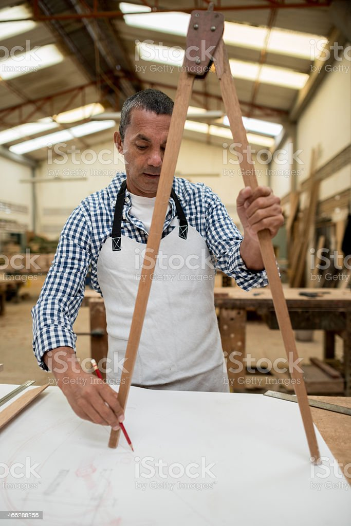 Carpenter working on a design with a compass stock photo