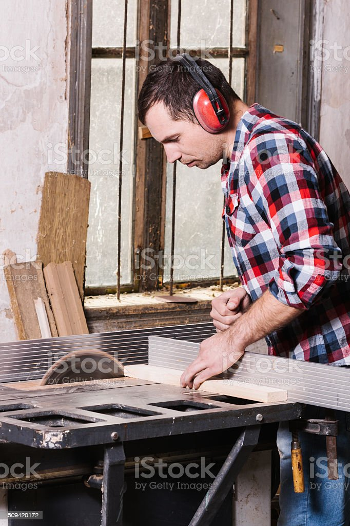 Carpenter working on an electric buzz saw cutting some boards royalty-free stock photo