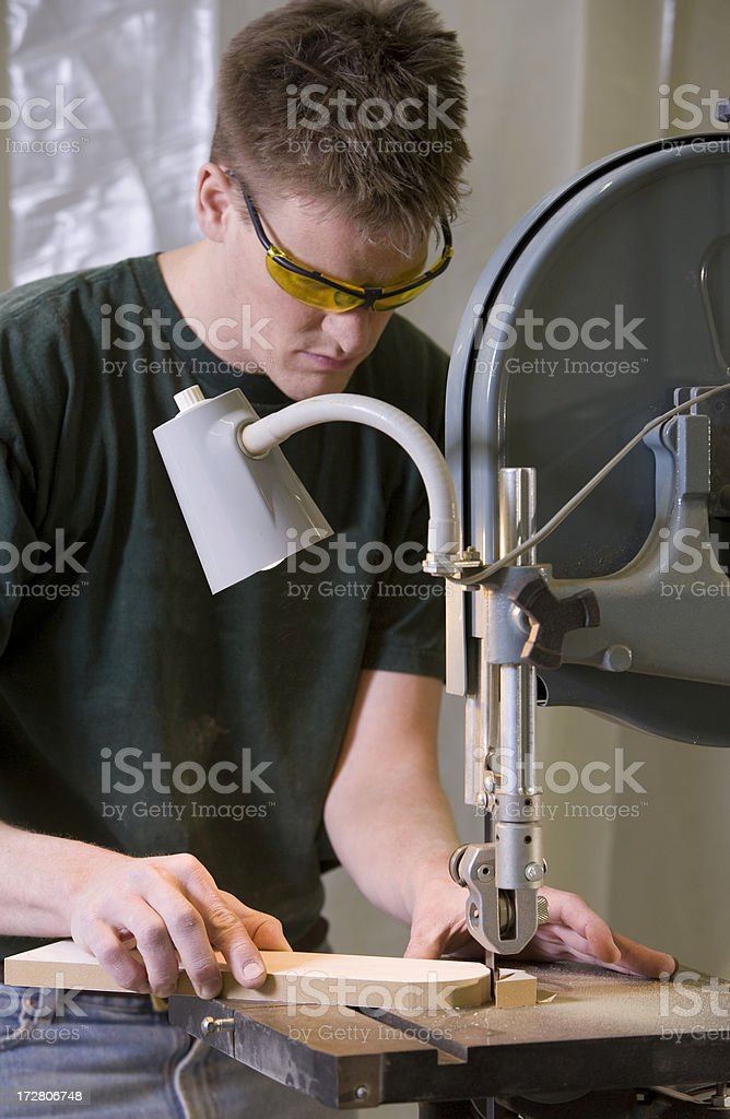 Carpenter working on band saw. stock photo