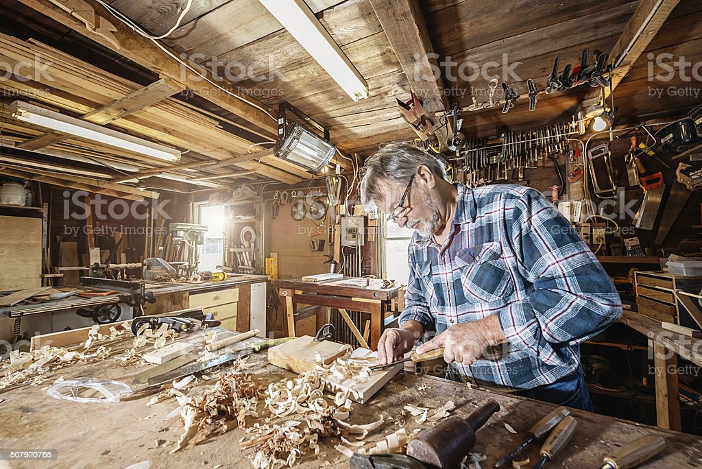 Carpenter working on wood with chisel stock photo