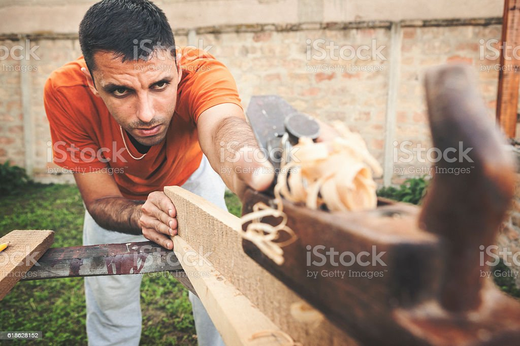 Carpenter working on wooden board stock photo
