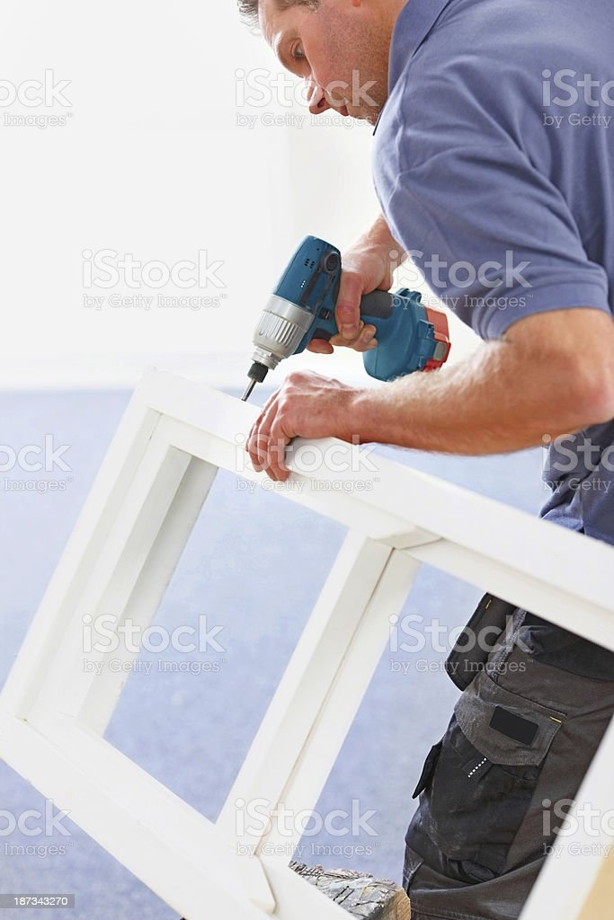 Carpenter working on wooden frame royalty-free stock photo