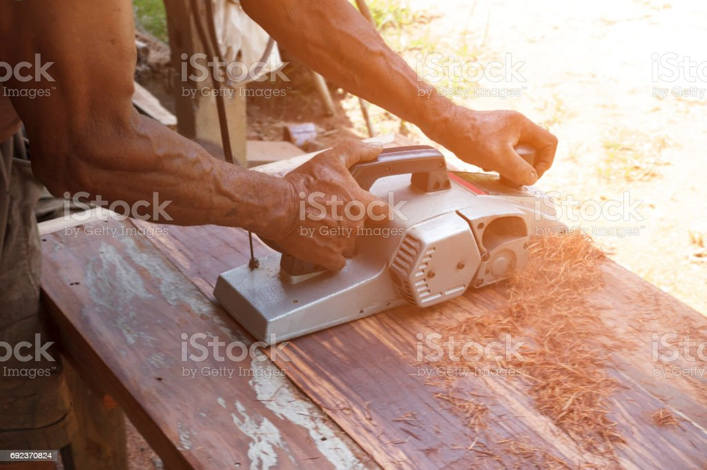 Carpenter working with electric planer on wooden plank. stock photo