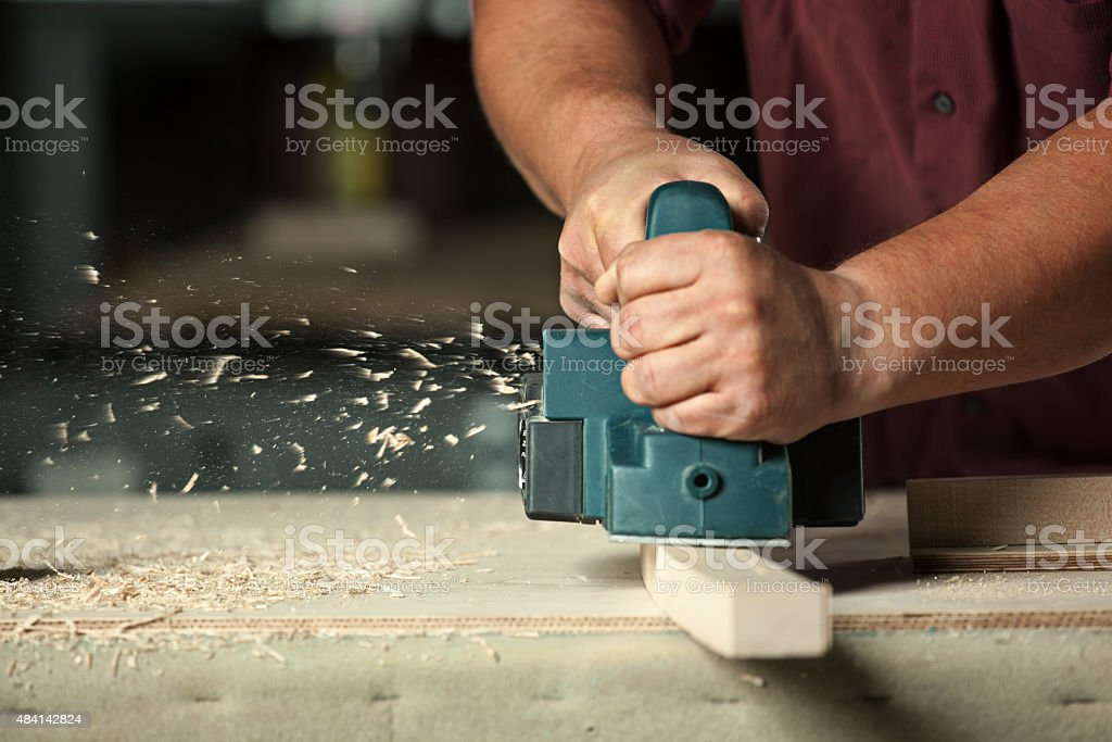 Carpenter working with electric planer. stock photo