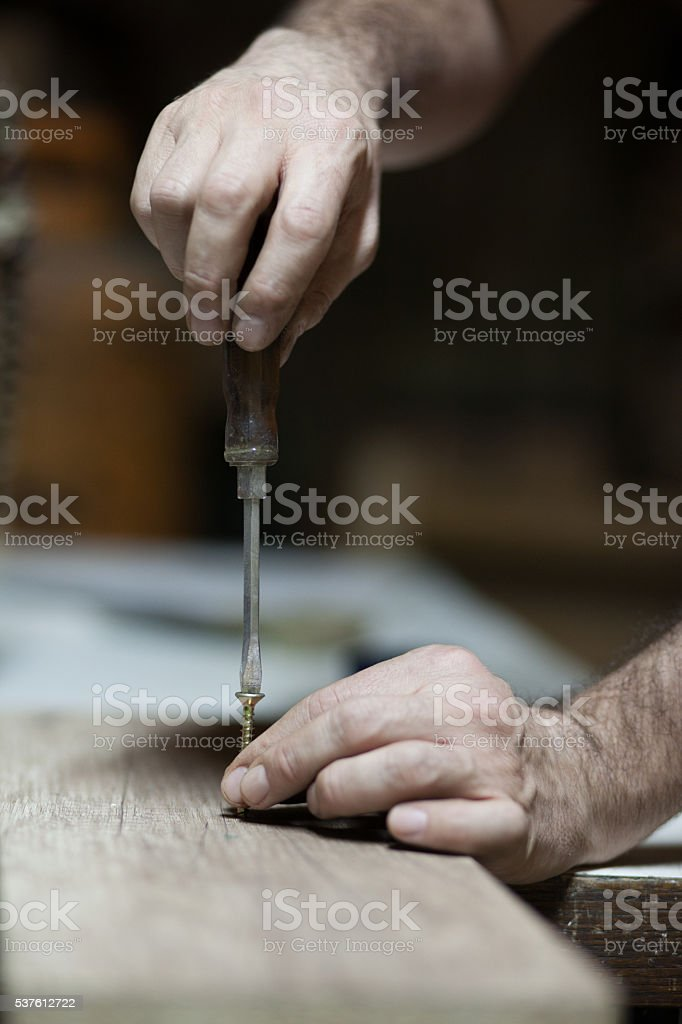 Carpenter working with svrewdriver stock photo