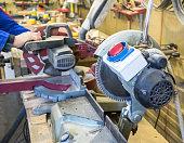 Carpenter workplace- Man using circular saw to cut wood