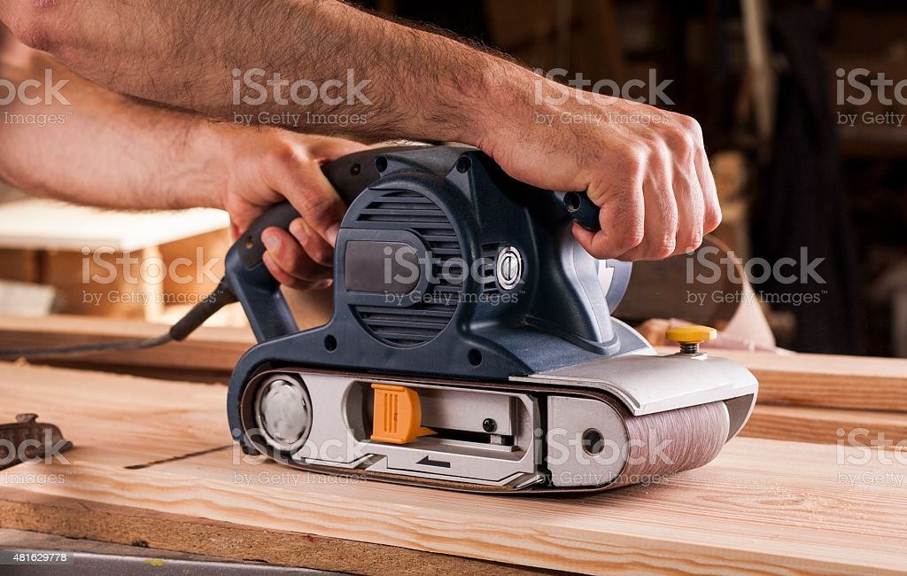 carpenter works with belt sander in carpentry stock photo