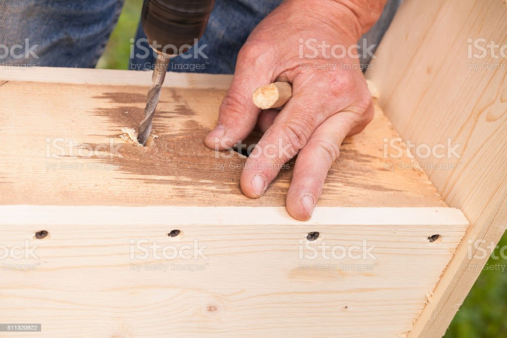 Carpenter works with drill, close-up photo stock photo