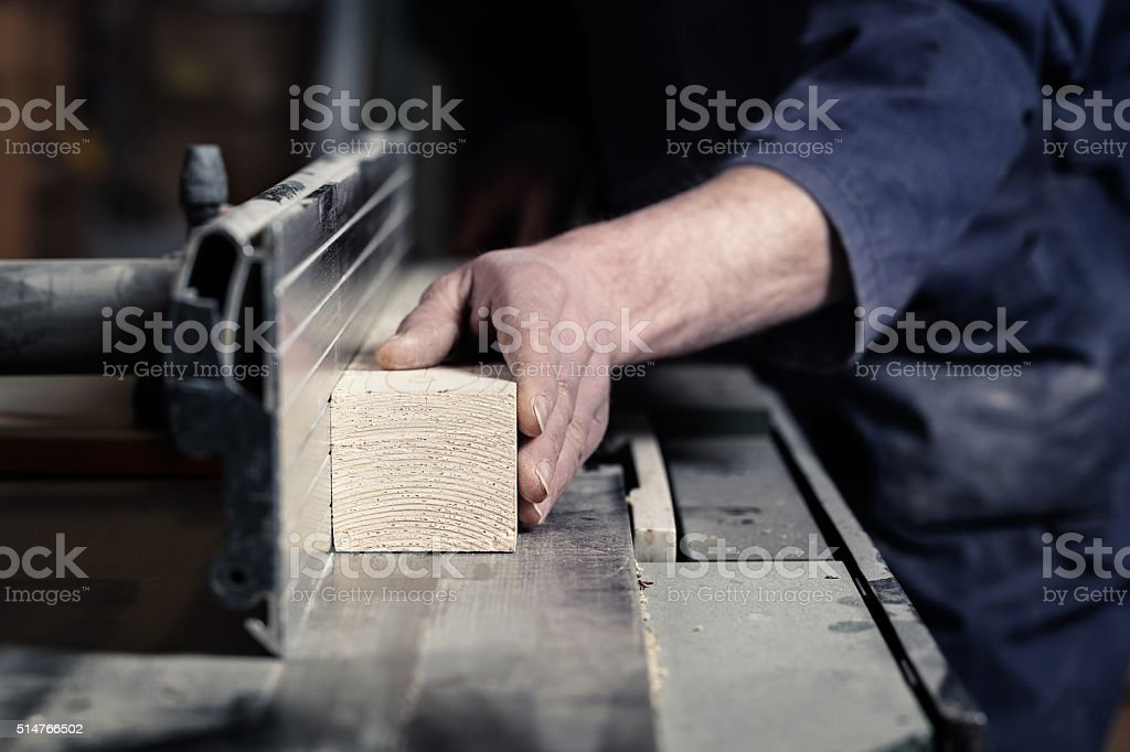 Carpenter's hands cutting wood with tablesaw stock photo