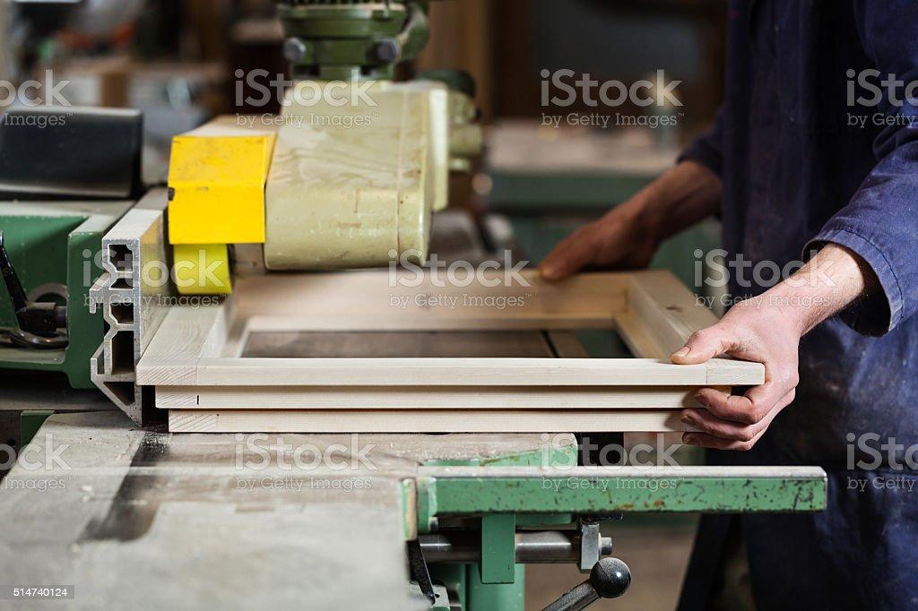 Carpenter's hands cutting wooden window frame stock photo