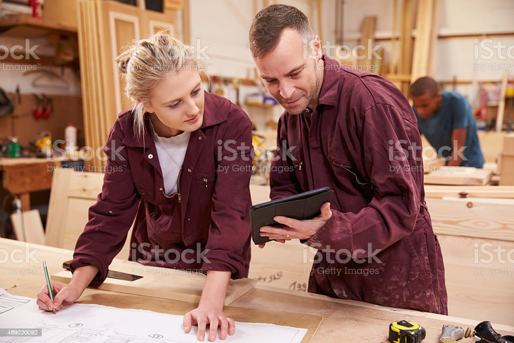 Carpenters wearing overalls looking at design plans stock photo