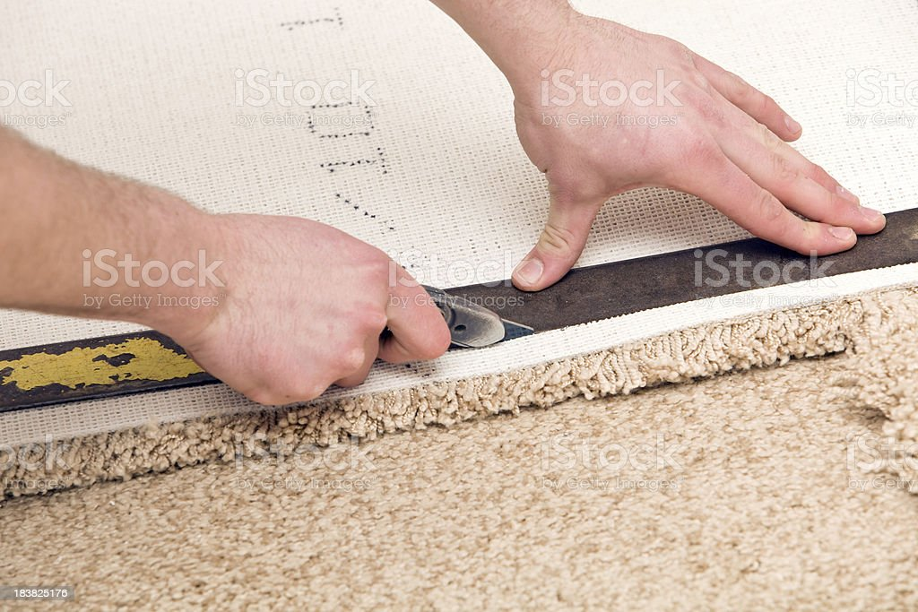 Carpet Installer Cutting with Knife and Straight Edge stock photo