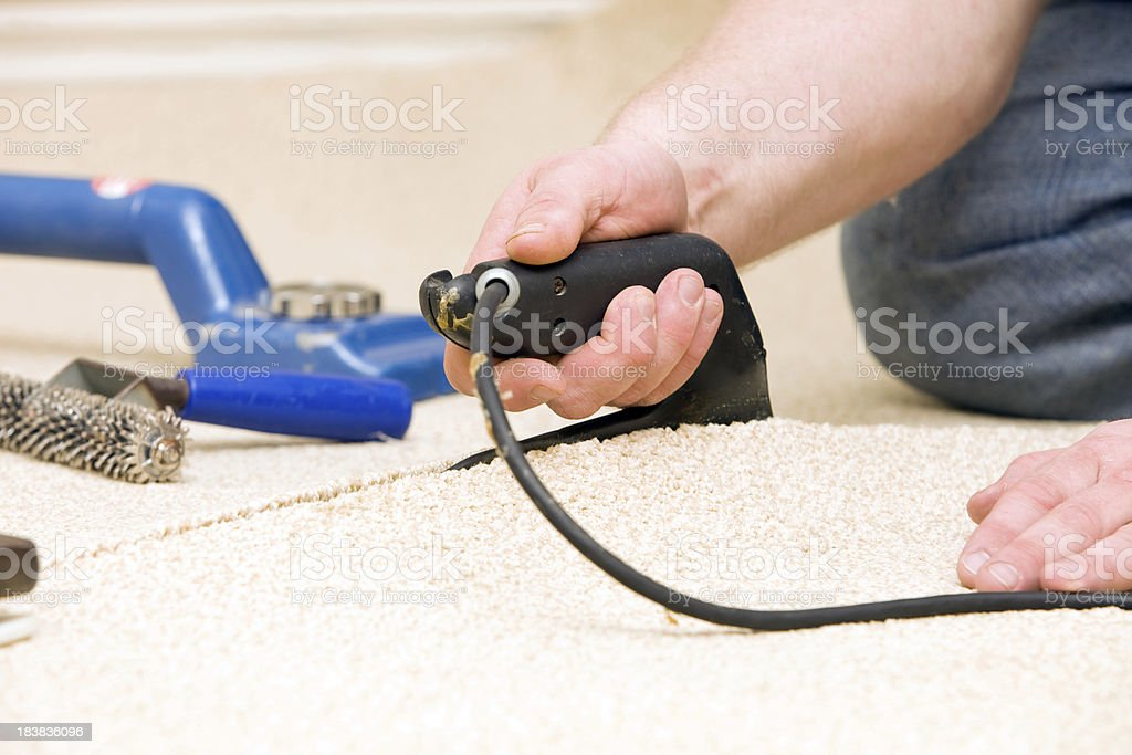Carpet Installer Joining Two Pieces with Seam Iron stock photo