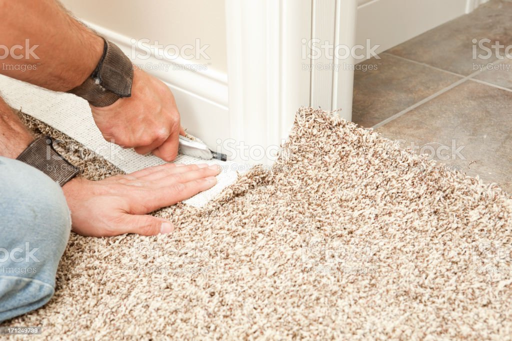 Carpet Installer Using Knife to Trim Wall Edge royalty-free stock photo