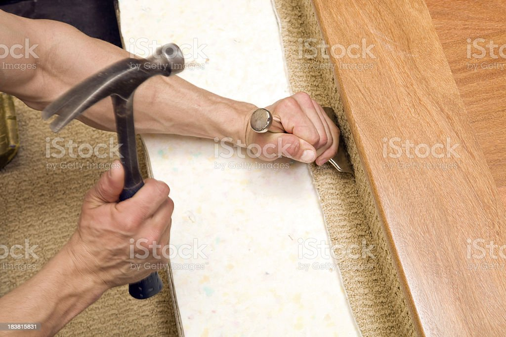 Carpet Installer Using Stair tool Near Hardwood Floor royalty-free stock photo