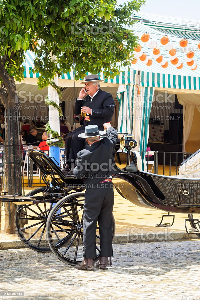 Carriage drivers dressed in tradional 'traje corto' with casetas behind stock photo