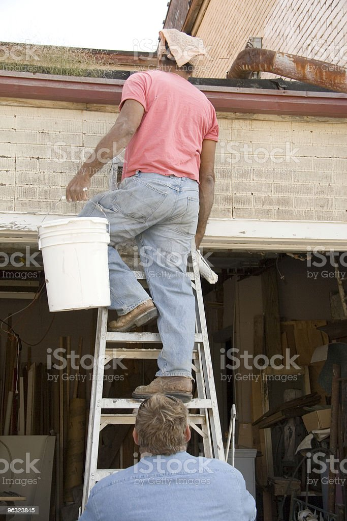 Carring Paint Bucket Down Ladder stock photo