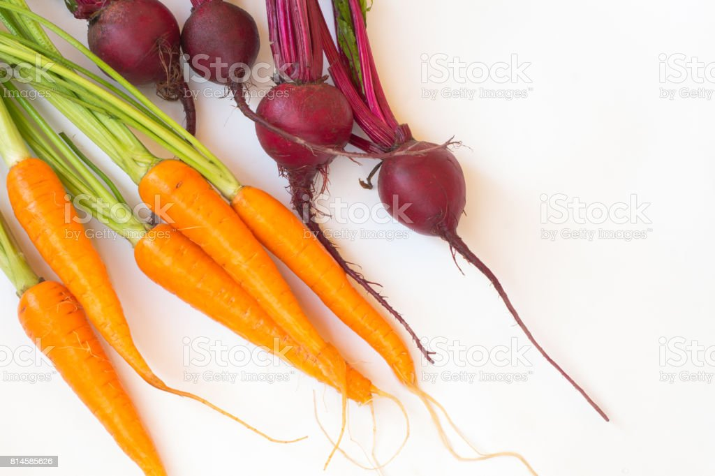 Carrot and beetroot with stems and leaves on a white background stock photo