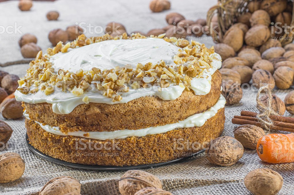 Carrot and Walnut Cake Topped with Cream  on Jute Background stock photo