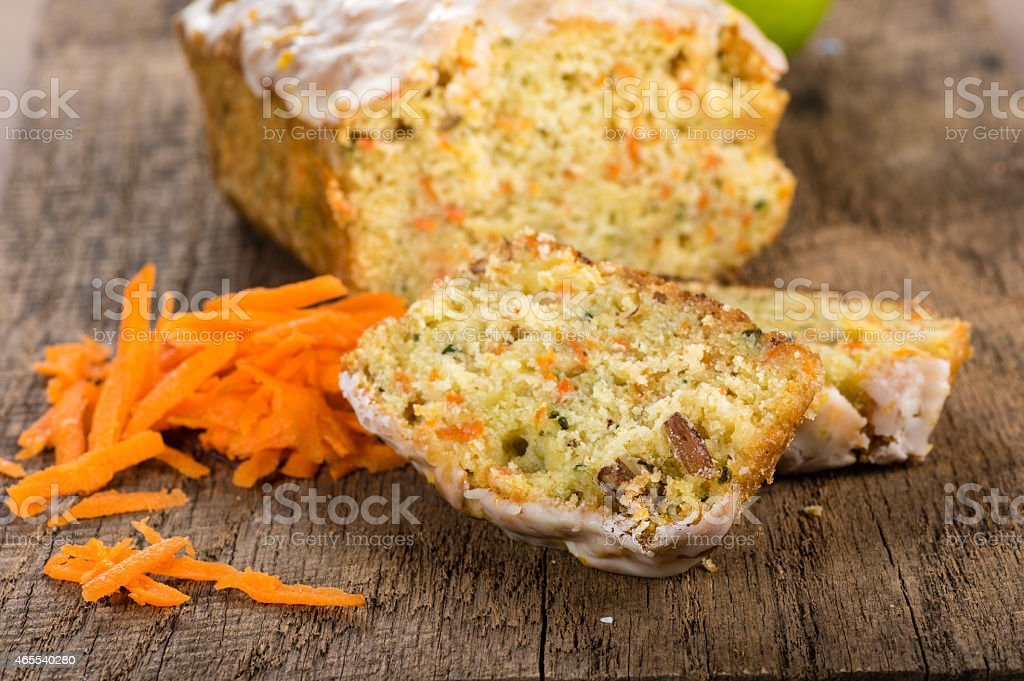Carrot apple cake on wooden table with shredded carrots