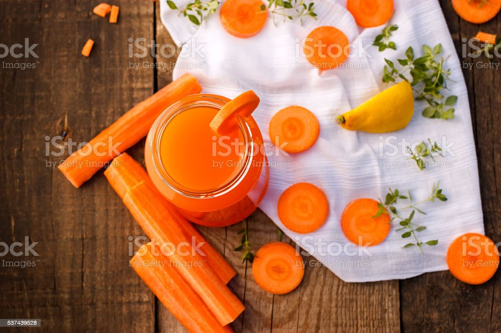 Carrot juice and slices of carrots stock photo