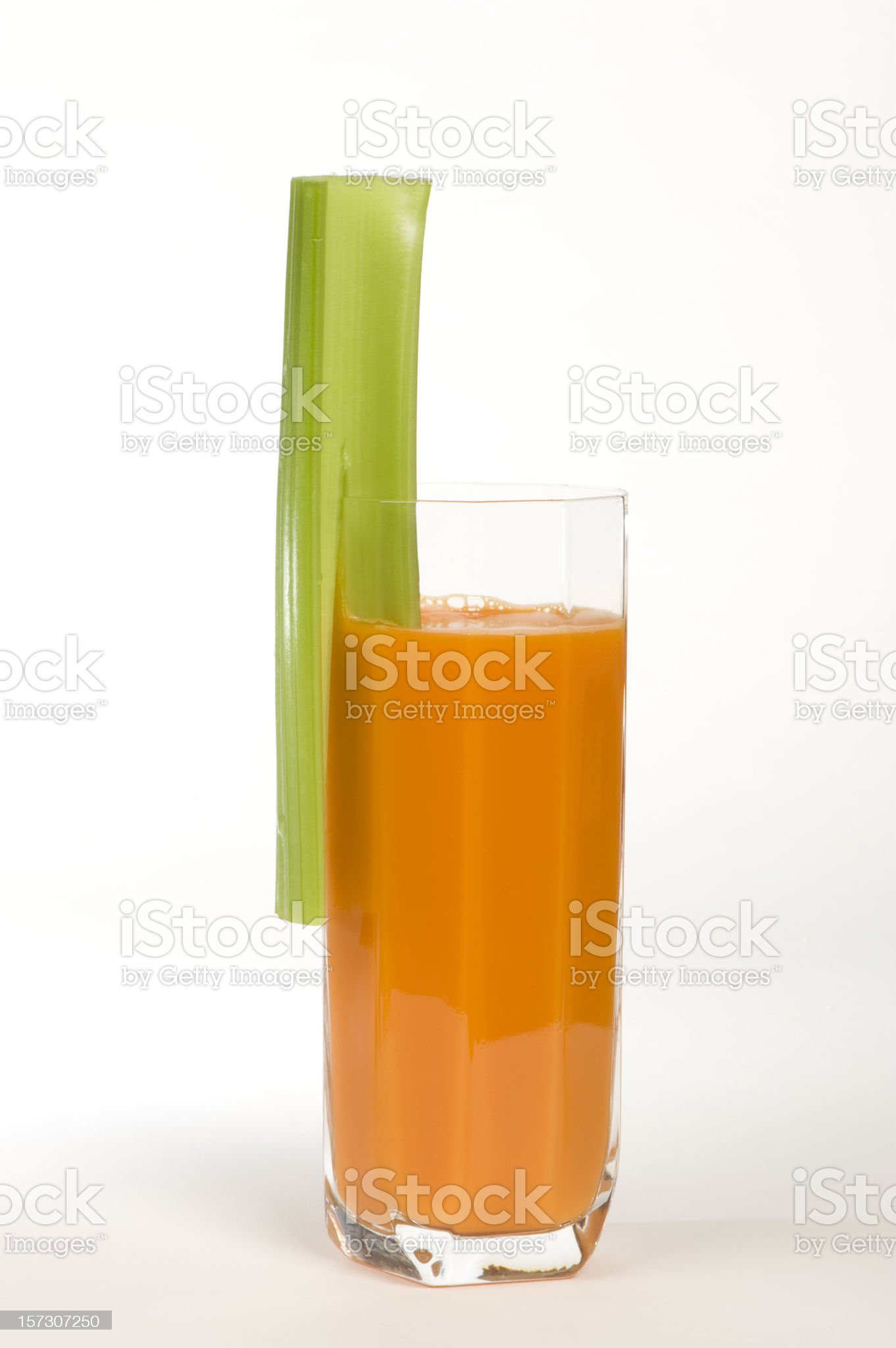 Carrot juice in a clear glass with stick of celery royalty-free stock photo