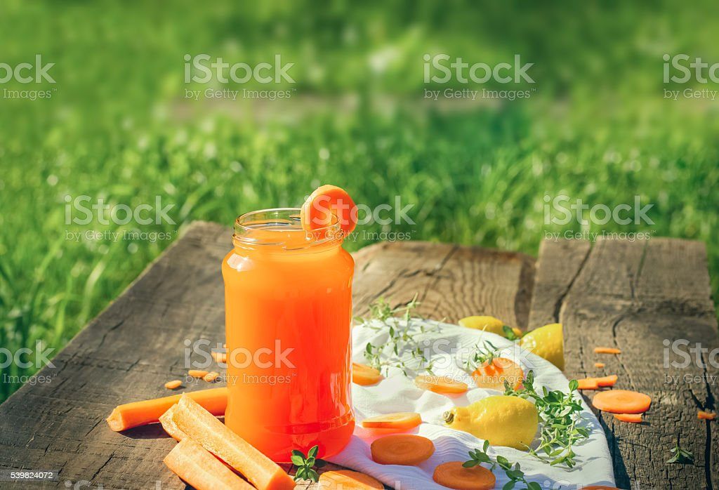 Carrot juice in jar - refreshing drink on rustic table stock photo