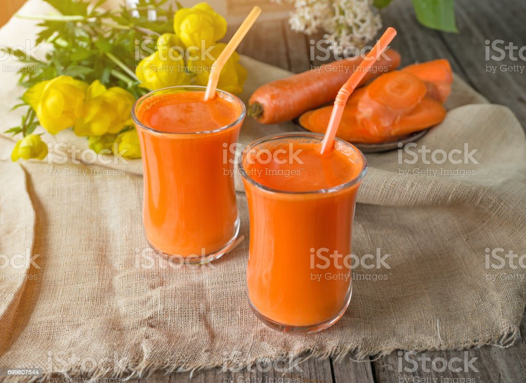 Carrot juice into two glass cups on a background of carrots and flowers in the early morning. The horizontal frame stock photo