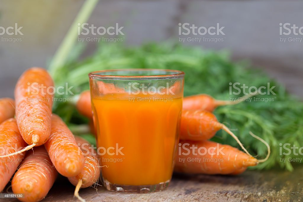 Carrot juice on wooden background stock photo