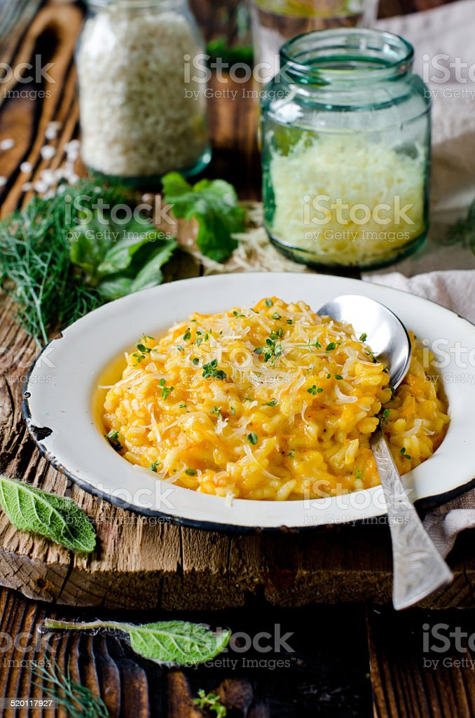 Carrot risotto in the plate on wooden table stock photo