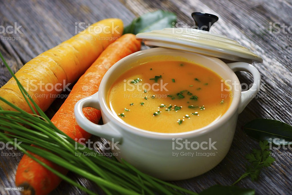 Carrot soup in a white bowl with lid and carrots on the side stock photo