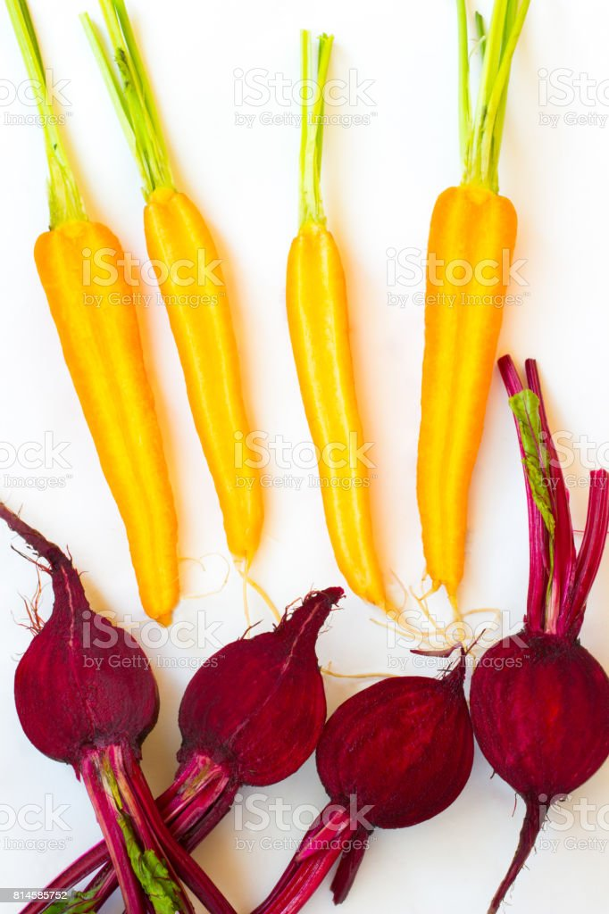 Carrots and beets with stems and leaves. Top view. White background stock photo
