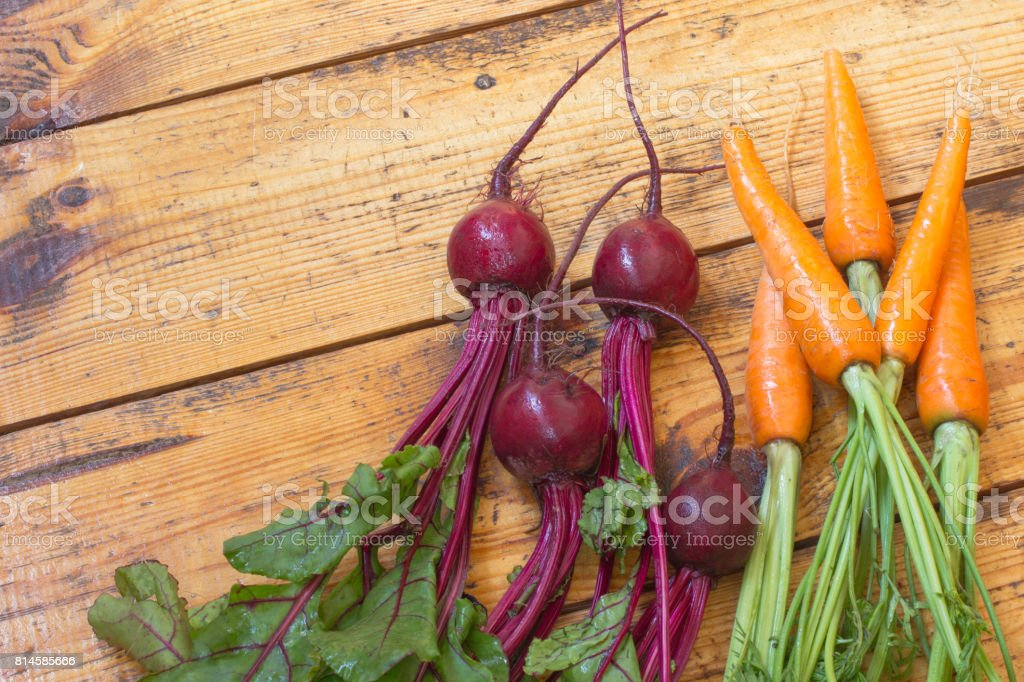 Carrots and Beets with stems and leaves. Top view. Wooden background stock photo