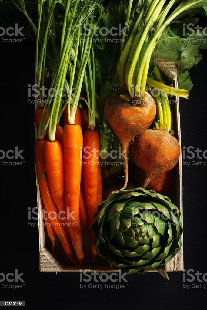 Carrots, turnips and an artichoke in a wooden box stock photo