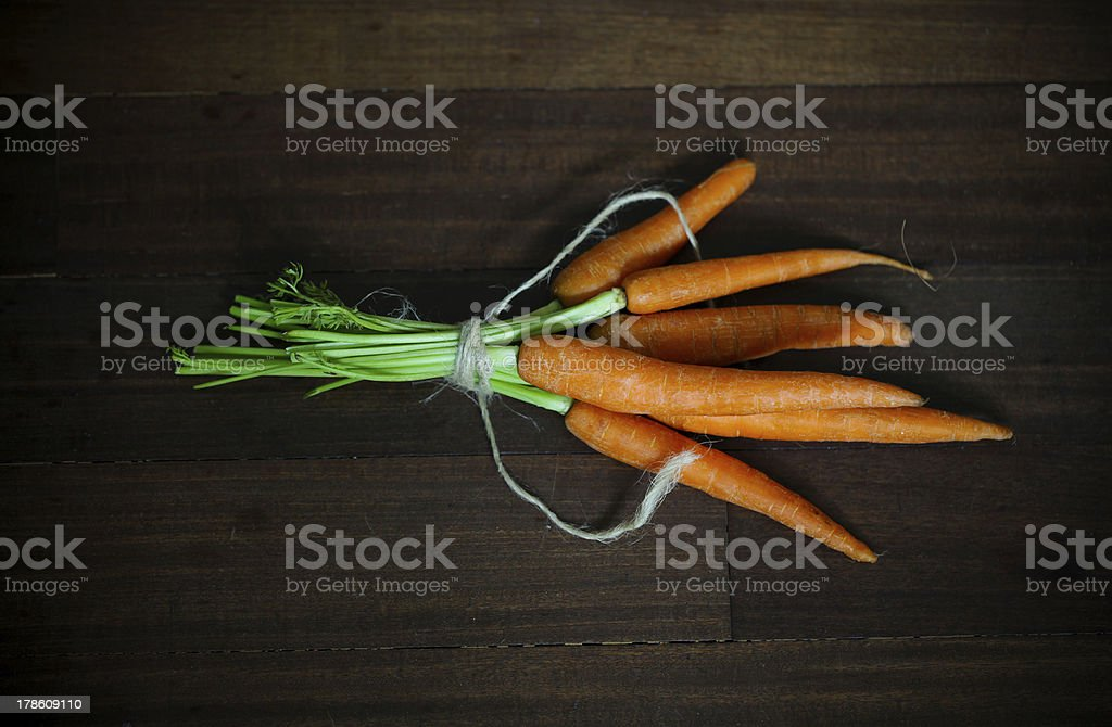 Carrots with greens, tied on brown wood royalty-free stock photo