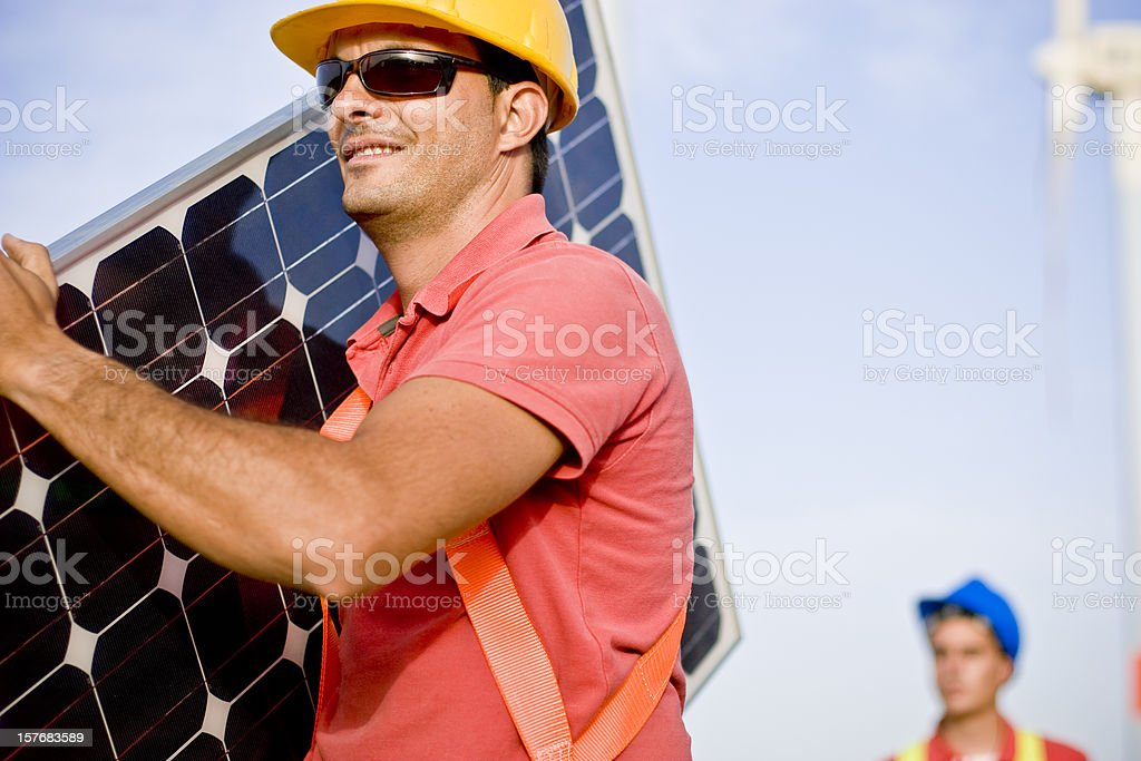 Carrying a photovoltaic panel royalty-free stock photo