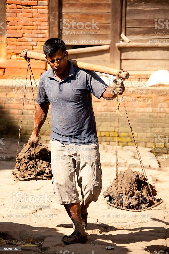 Carrying clay to be prepared for pottery. stock photo