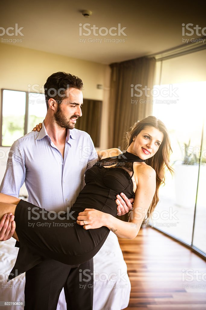 carrying the wife in the hotel room stock photo