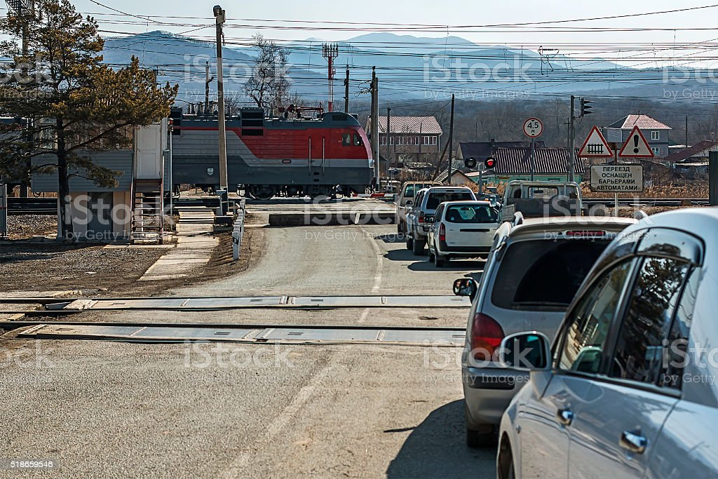 cars are at a railway crossing stock photo