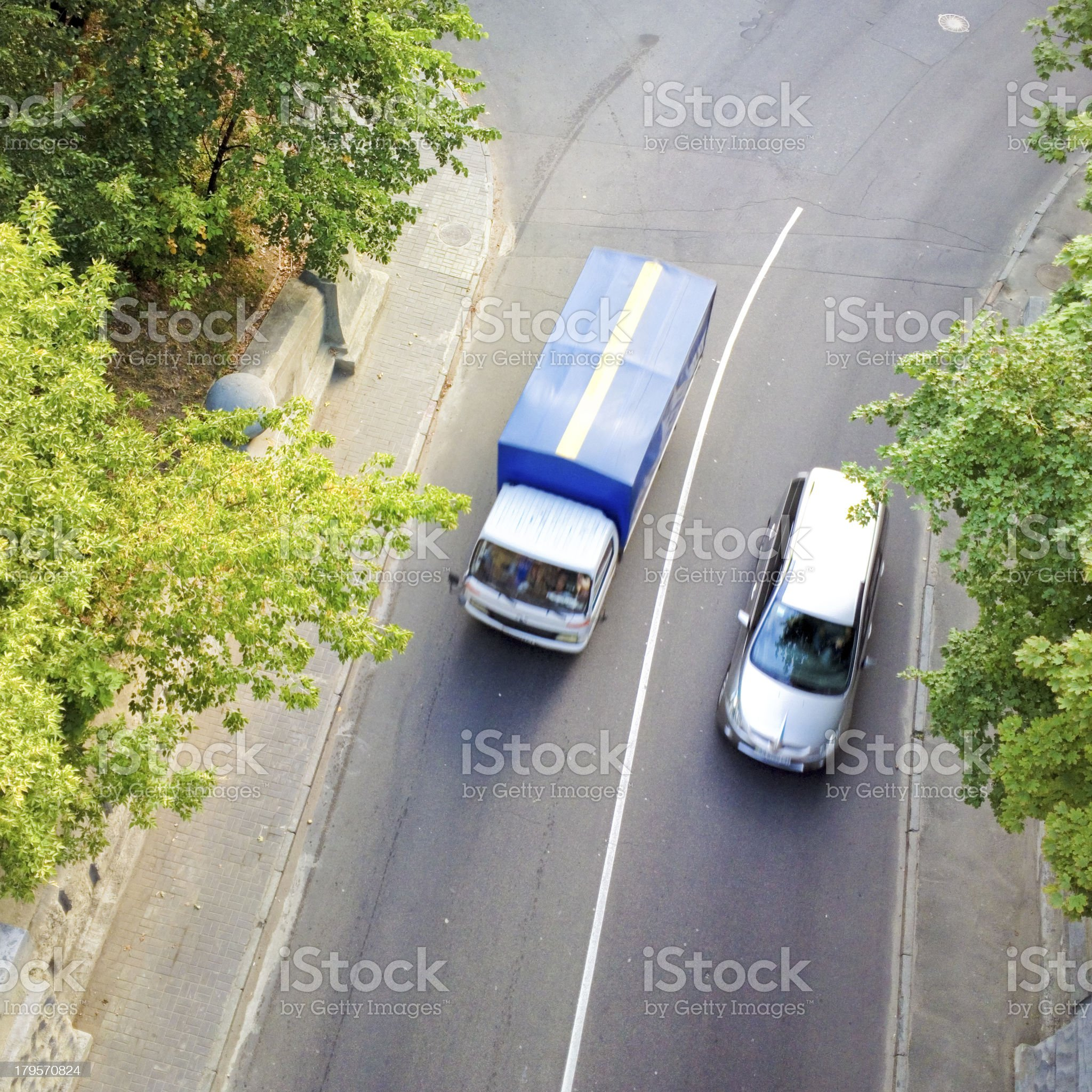 Cars driving along a tree road. royalty-free stock photo