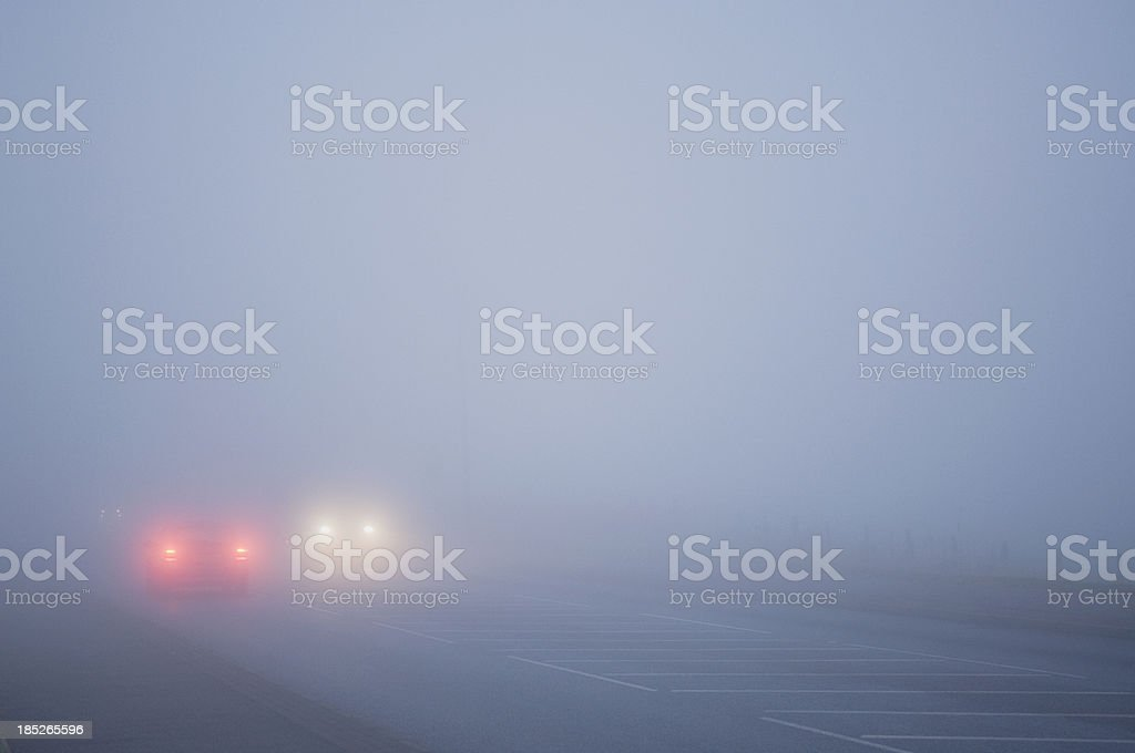 Cars driving in thick fog royalty-free stock photo