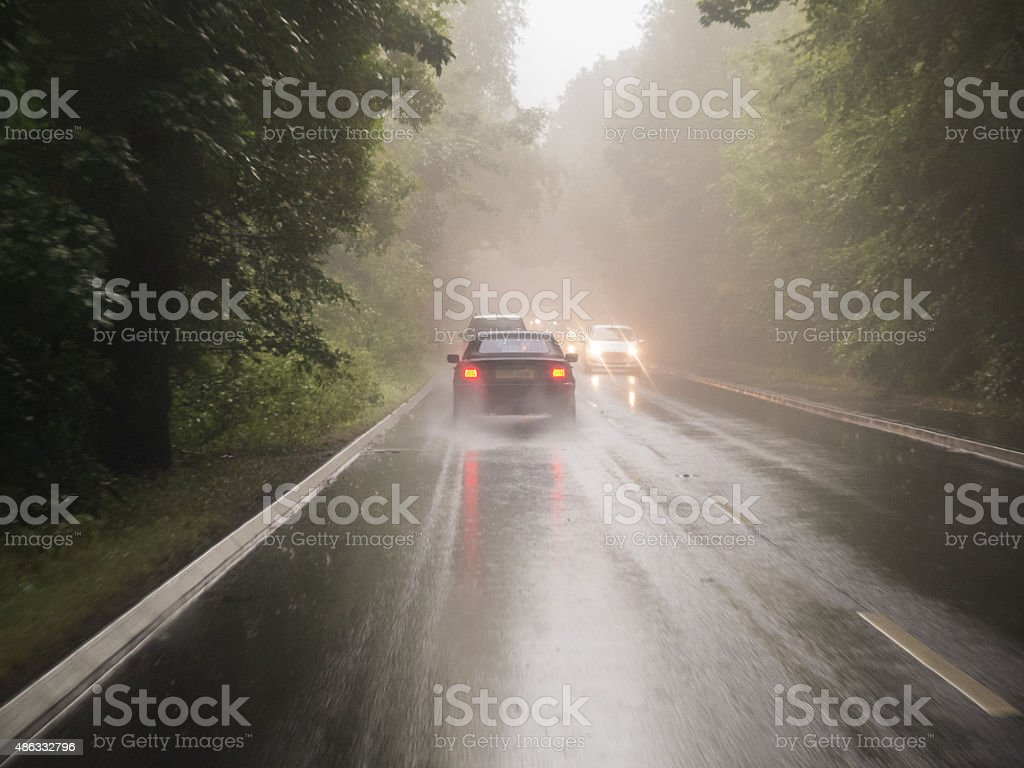 Cars driving on a wet road through woodland stock photo