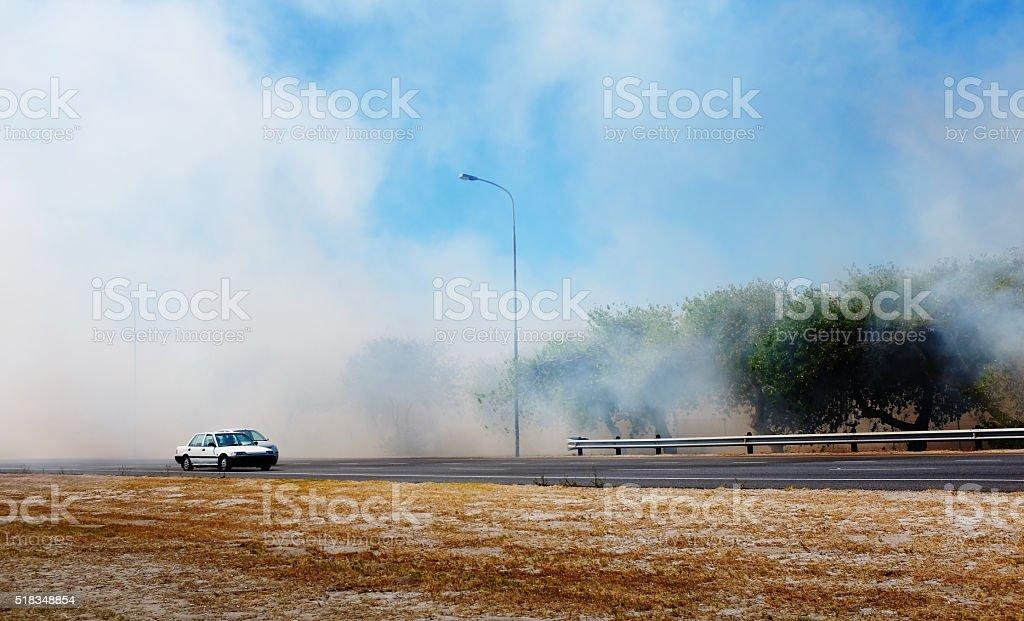 Cars driving through smoke from brushfire stock photo