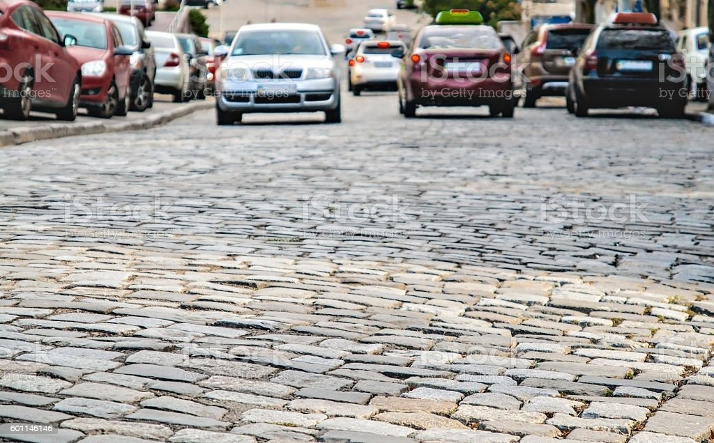 cars go on the road cobbles stock photo
