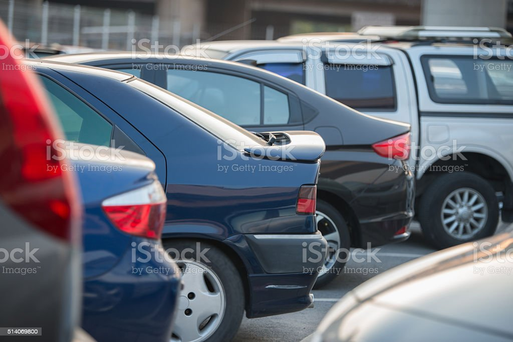 cars in a row on a parking lot stock photo