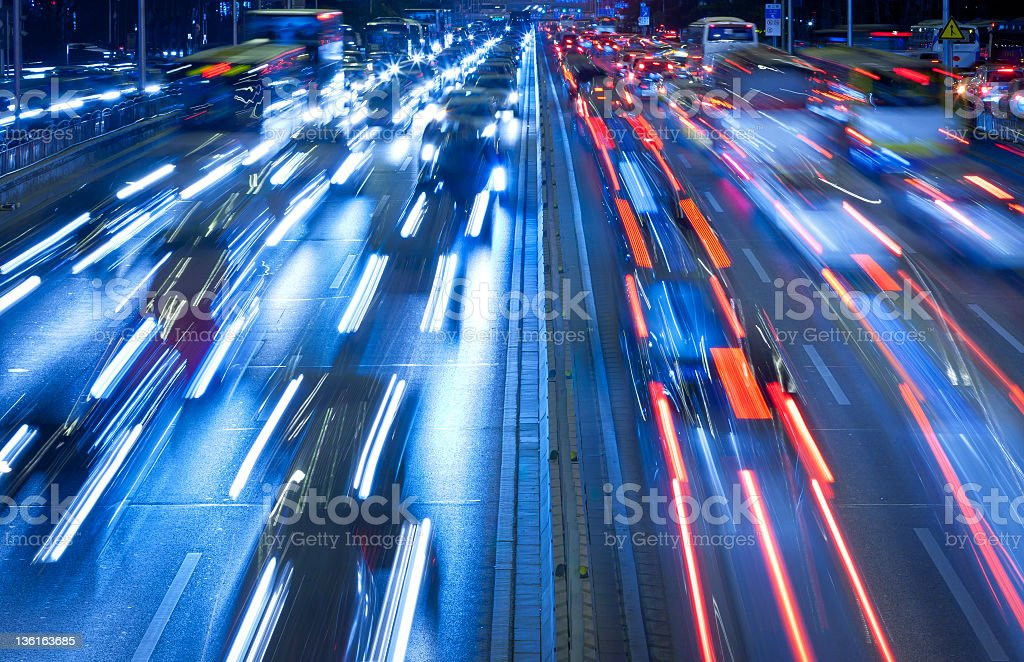 Cars in motion at night on a speeding city highway stock photo