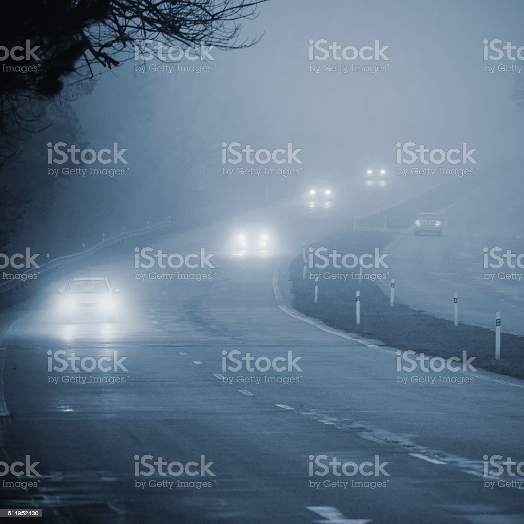 Cars in the fog. Bad winter weather and dangerous traffic. stock photo