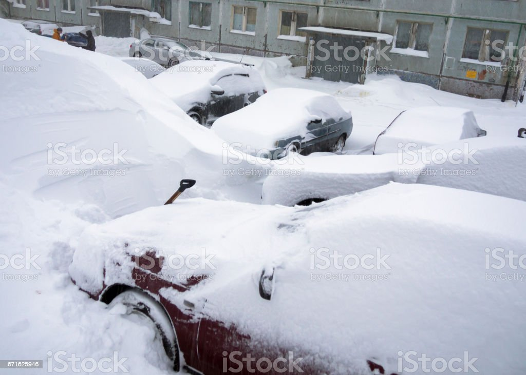 Cars stand in the yard of the house, covered with snow stock photo